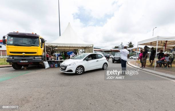 A man directs traffic at a road block on March 26 in Cayenne French Guiana during a string of regionwide protests and road blockades Road blockades...