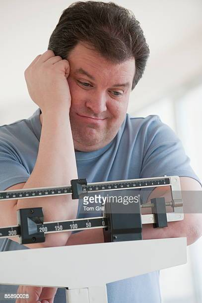 man disappointed in weight on scale