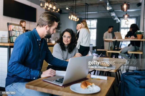 Man Discussing Work With Colleague At A Busy Business Cafe