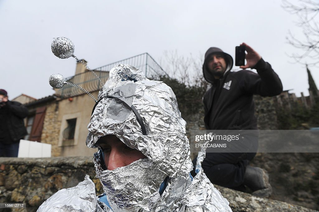 A man disguise in 'martian' walks, on December 21, 2012, in the street of the French southwestern village of Bugarach, near the 1,231 meter high peak of Bugarach - one of the few places on Earth some believe will be spared when the world allegedly ends today according to claims regarding the ancient Mayan calendar. French authorities have pleaded with New Age fanatics, sightseers and media crews not to converge on the tiny village.