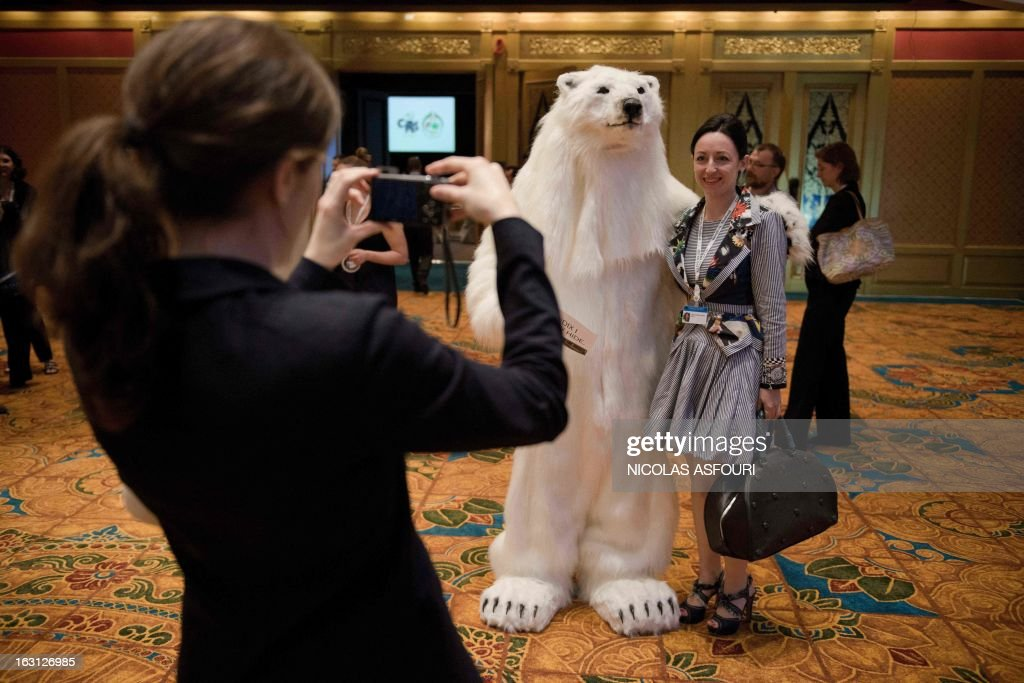 A man disguised as a bear poses for photographs as a cocktail and photo exhibition, held by Russia and international NGO's takes place at the Convention on International Trade in Endangered Species (CITES) in Bangkok on March 5, 2013. Global conservationists converged on Bangkok on March 3 for the start of endangered species talks, as host Thailand was forced onto the defensive over the rampant smuggling of ivory through its territory. AFP PHOTO/ Nicolas ASFOURI