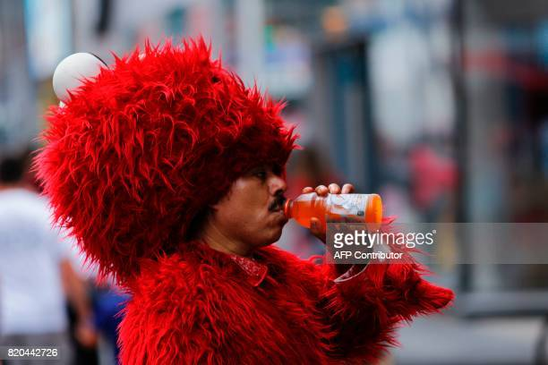 A man disguised as Elmo drinks to keep hydrated at Times Square during a sunny day as hot temperatures continue in New York on July 21 2017 / AFP...