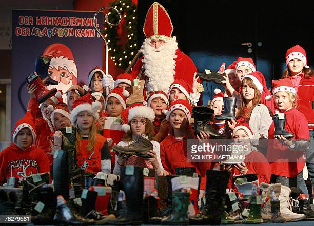 A man disguised as Santa Claus and children pose amid of Santa boots filled with candies 06 December 2007 at the 'Theater am Marientor' theatre in...
