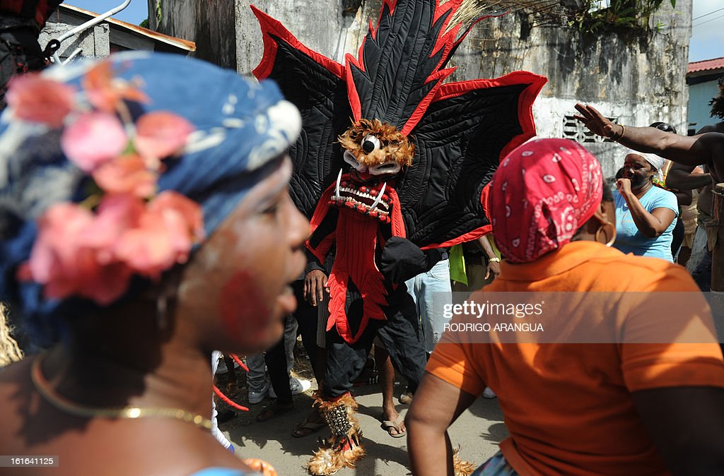 A man disguised as the devil confronts a pedestrian during the so called 'Congos y Diablo', Congos and Devil, carnival ritual in Nombre de Dios 120 km north to Panama City on February 13, 2013 . The celebration dates to colonial times with devils representing the Spanish conquerors and the 'Congos' African slaves. AFP PHOTO/ Rodrigo ARANGUA