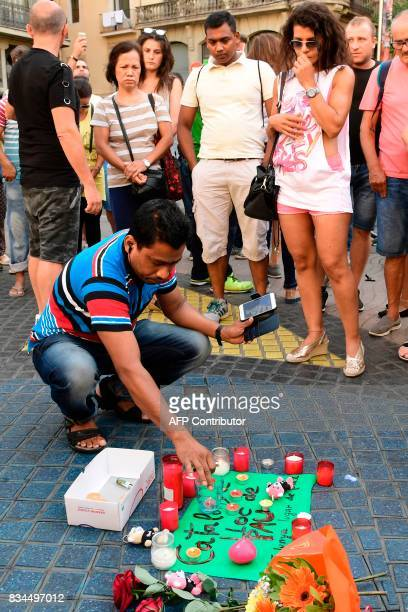 A man displays a candle next to first flowers and a message to the victims on August 18 2017 on the spot where yesterday a van ploughed into the...