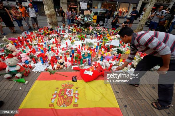 TOPSHOT A man displays a candle to pay tribute to the victims of the Barcelona attack on Las Ramblas boulevard in Barcelona on August 19 two days...