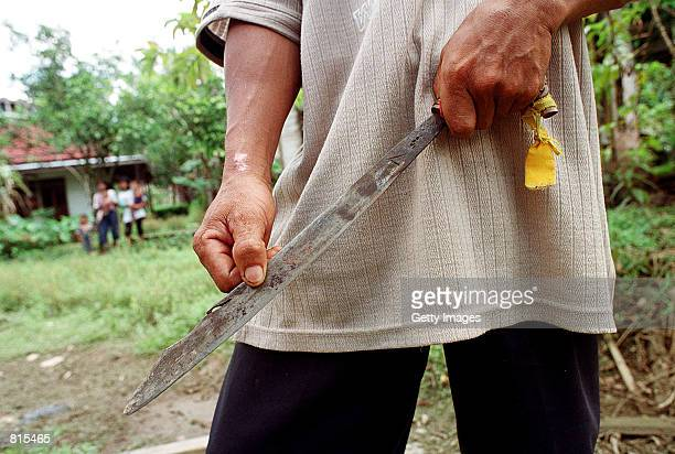 A man displays a long knife a traditional Dayak tool used for everyday chores that is now being employed to kill Ethnic Madurese March 6 2001 in the...