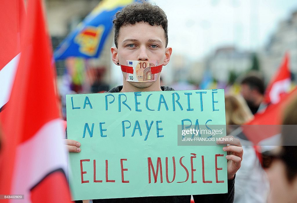 A man displays a placard which translates as ' precarity doesn't pay, it muzzles' during a protest against controversial labour reforms on June 28, 2016 in Rennes. / AFP / JEAN