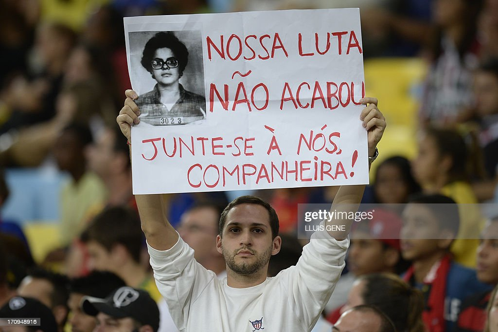 A man displays a poster with a police mugshot of now Brazilian President Dilma Rousseff reading 'The fight is not over. Join us Comrade!' during the FIFA Confederations Cup Brazil 2013 Group B football match between Spain and Tahiti, at the Maracana Stadium in Rio de Janeiro on June 20, 2013. Brazilians took to the streets again Thursday in several cities on a new day of mass nationwide protests, demanding better public services and bemoaning massive spending to stage the World Cup. AFP PHOTO / LLUIS GENE