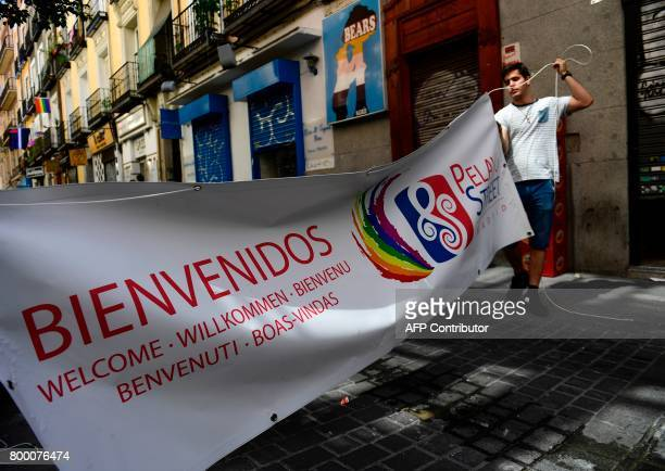 A man displays a welcoming banner in Madrid's Chueca district on June 23 2017 during the WorldPride 2017 Some three million revellers are expected in...