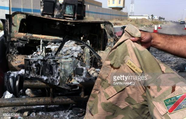 A man displays an Iraqi army jacket in front of a burnt out USmade Iraqi army HUMVEE vehicle at the Kukjali Iraqi Army checkpoint some 10km of east...