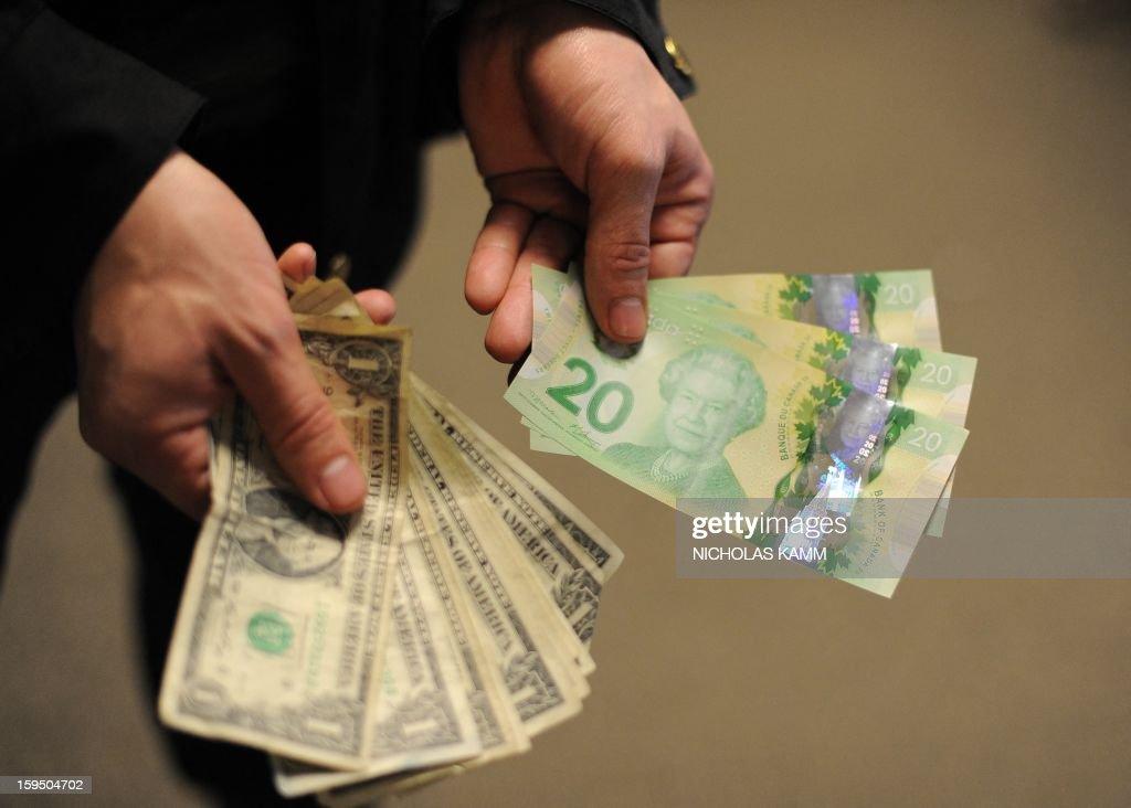 A man displays Canadian 20-dollar bills and US one-dollar bills in Washington on January 14, 2013. AFP PHOTO/Nicholas KAMM