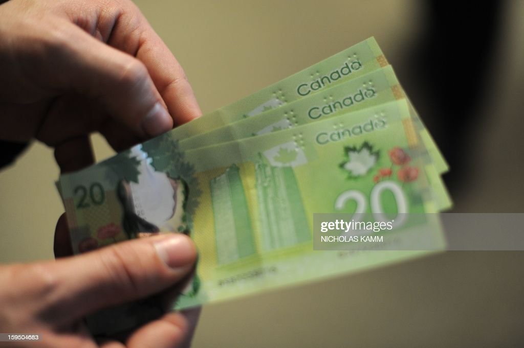 A man displays Canadian 20-dollar bills in Washington on January 14, 2013. AFP PHOTO/Nicholas KAMM