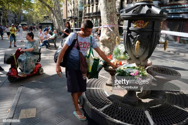 A man displays flowers at the Canaletas fountain on the Rambla boulevard on August 18 a day after a van ploughed into the crowd killing 13 persons...