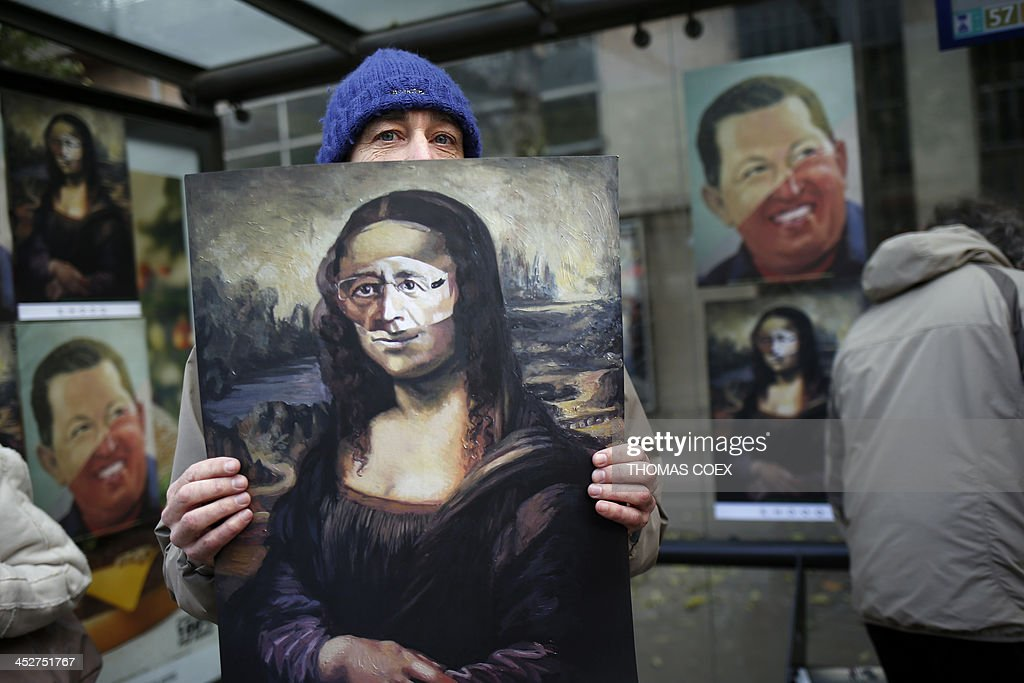 A man displays his caricatural paintings of Hugo Chavez and Francois Hollandeon the sidelines of a demonstration for a 'tax revolution' gathering thousands of people called by the 'Front de gauche' movement on December 1, 2013 in Paris.