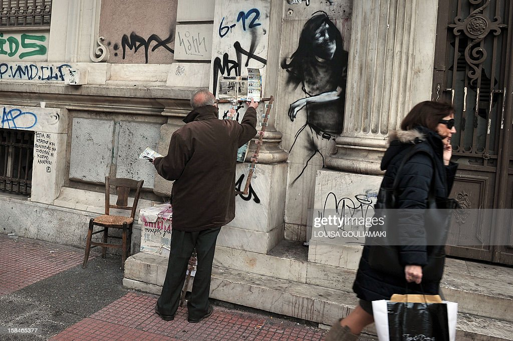 A man displays lottery tickets for sale next to a graffiti in Athens on December 17, 2012.