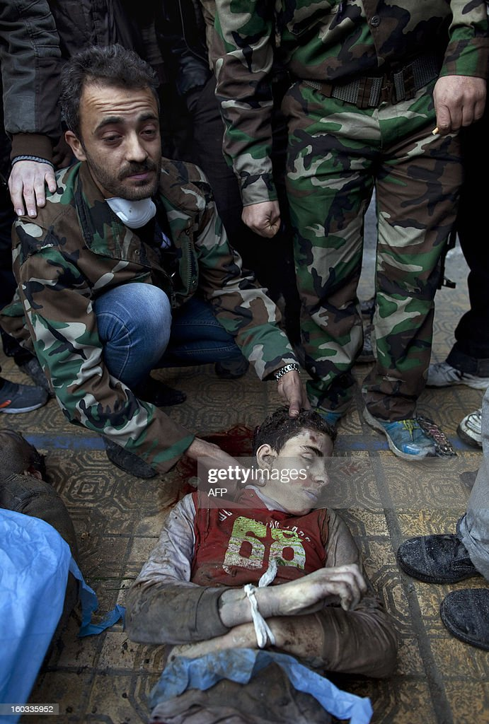 A man displays the body of a young Syrian civilian, executed and dumped in the Quweiq river, as it lays in the grounds of the courtyard of a Yarmouk School, in the Bustan al-Qasr district of Aleppo, on January 29, 2013. The bodies of at least 65 young men, all executed with a single gunshot to the head or neck, were found in a river in Aleppo city, adding to the grim list of massacres committed during Syria's 22-month conflict. AFP PHOTO/JM LOPEZ