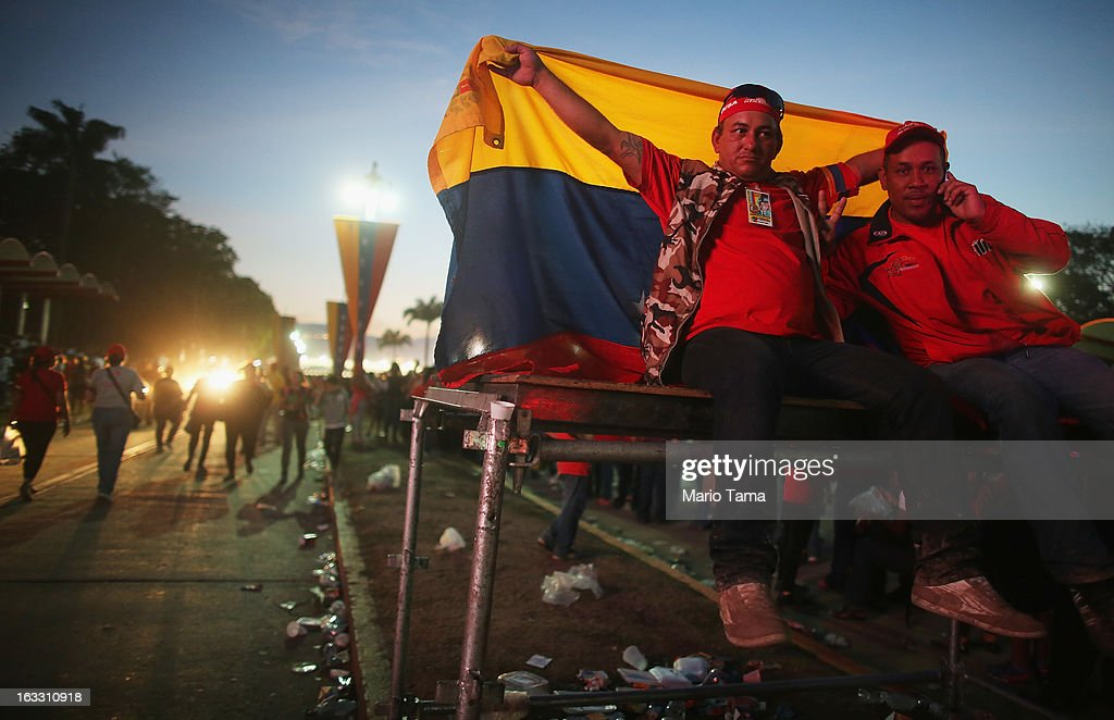 A man displays the national flag as others gather and wait in line to view the remains of late Venezuelan President Hugo Chavez outside the Military Academy on March 7, 2013 in Caracas, Venezuela. Countless Venezuelans waited on a mile-long line to pay their last respects to Chavez before his funeral tomorrow.