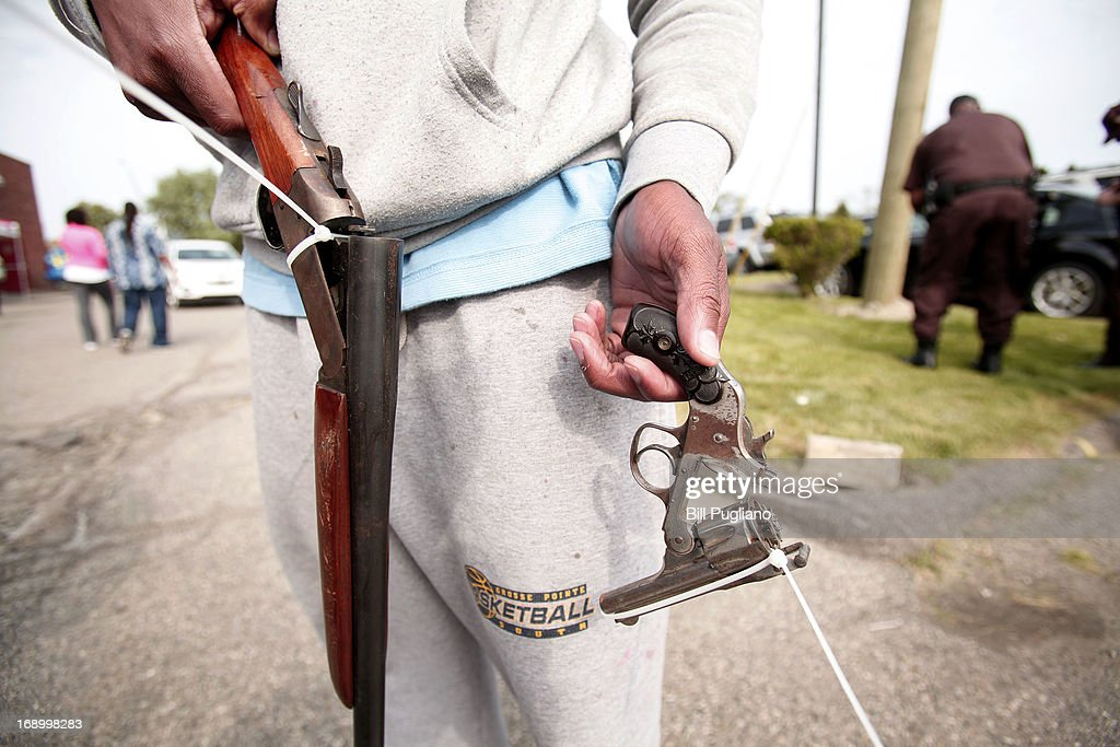 A man displays two guns he is bringing in to exchange for two $50 Meijer gift cards at a 'Groceries For Guns' gun buyback program May 18, 2013 at the New St. Paul Tabernacle Church of God in Christ in Detroit, Michigan. The event was sponsored by the law firm Goodman Acker P.C. in a public-private partnership with Wayne County.