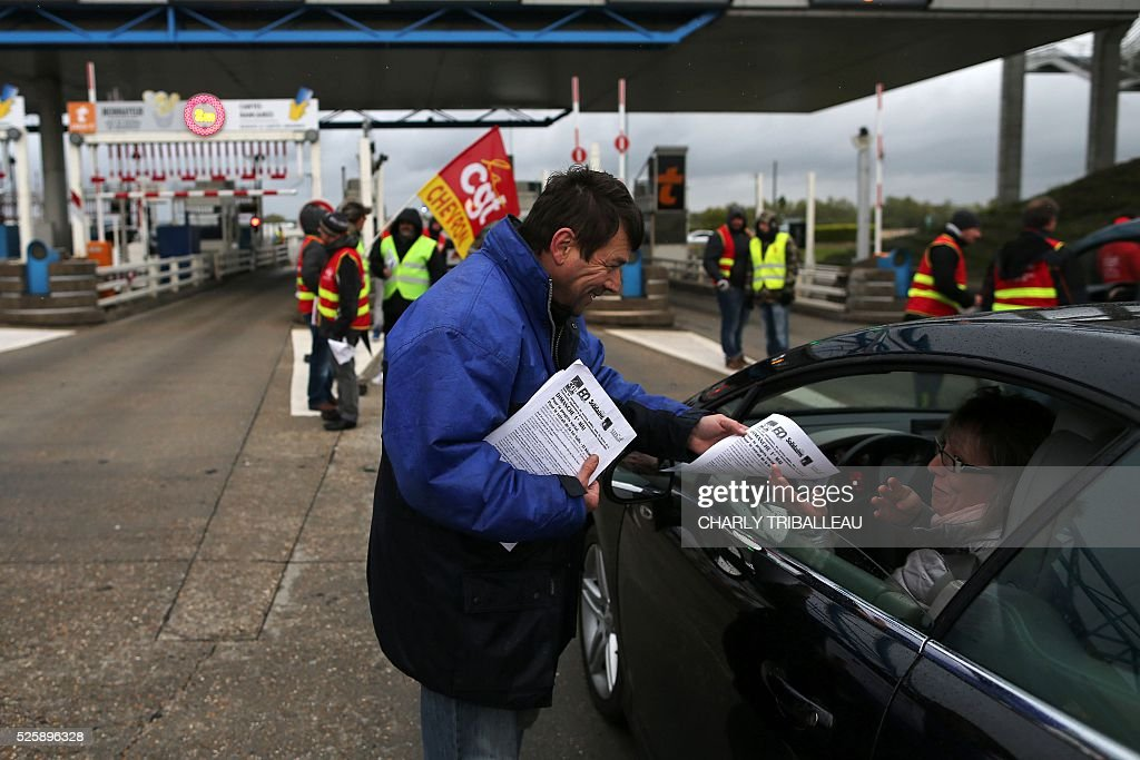 A man distributes flyers next to people wearing waistcoats of the French CGT Trade Union as they block the road at a toll booth on the Normandy Bridge in Le Havre, northwestern France, on April 29, 2016 during a demonstration against the new labour draft-law. / AFP / CHARLY