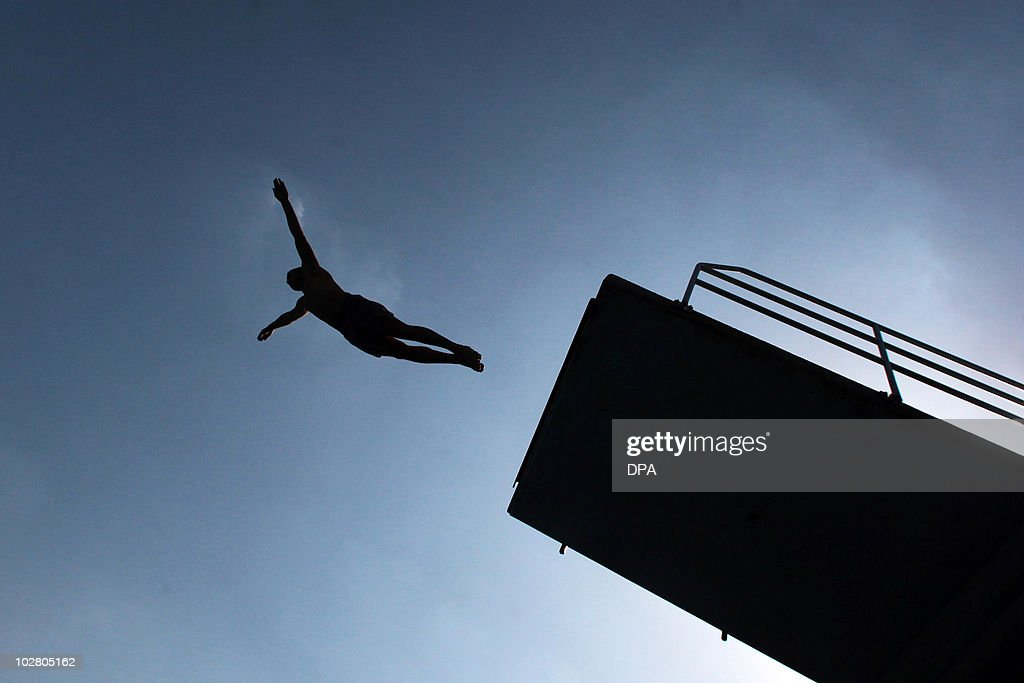 A man dives in to a swimming pool on July 10, 2010in the central German city of Frankfurt am Main as the country is experiencing a heat-wave with temperatures reaching 37 degrees centigrade. AFP PHOTO / FREDRIK VON ERICHSEN GERMANY OUT