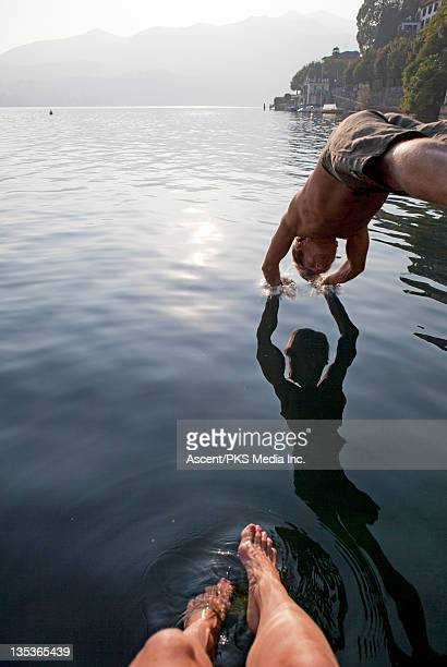 Man dives into tranquil lake while woman watches
