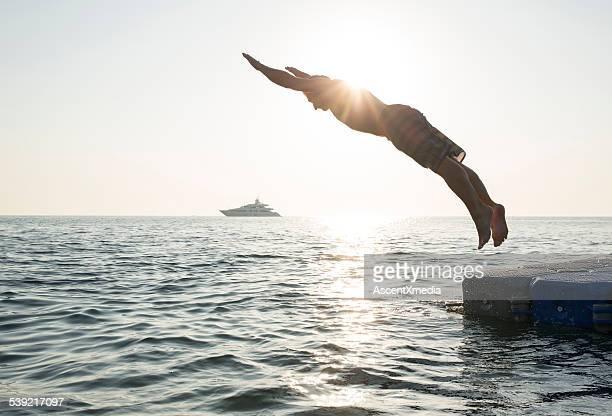 Uomo immersioni in mare tranquillo, dal molo e barca