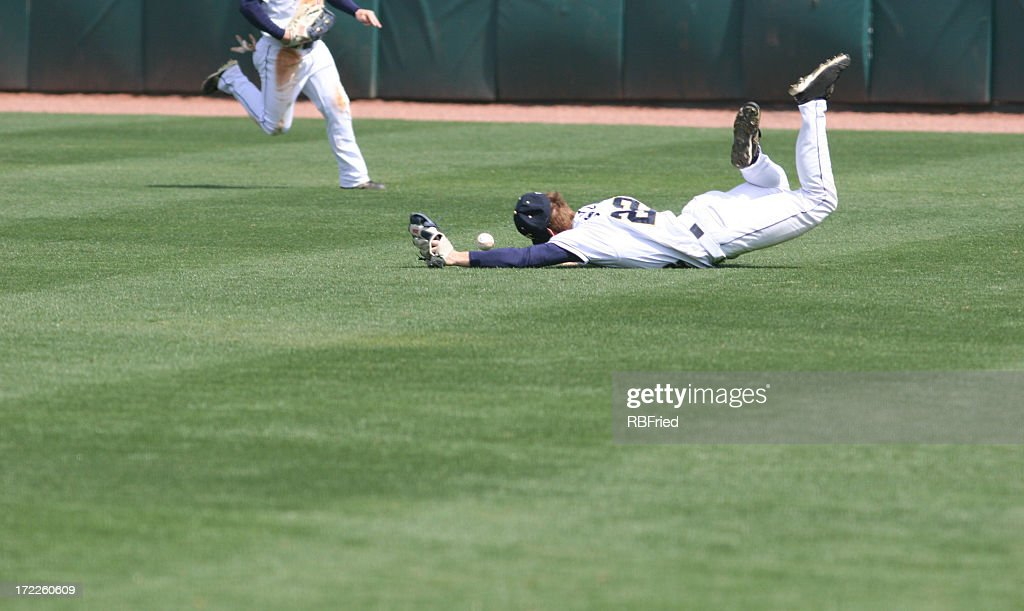 Man diving and missing the catch in baseball : Stock Photo