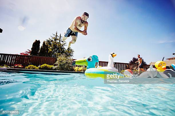 Man diving from pool deck towards pool toy
