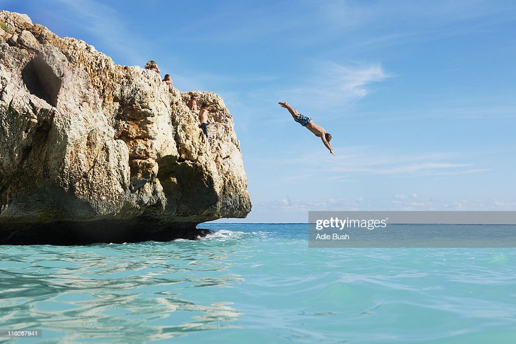 Man diving from rocks into the sea : Stock Photo