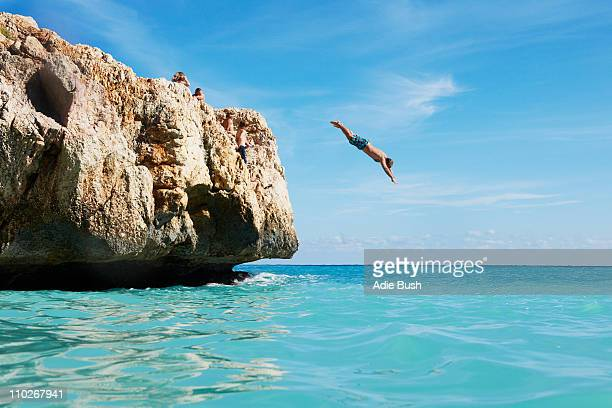 Man diving from rocks into the sea