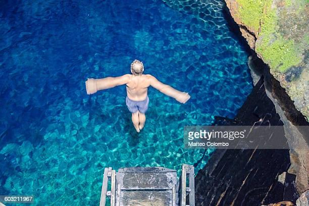 Man diving into a cenote, Yucatan, Mexico