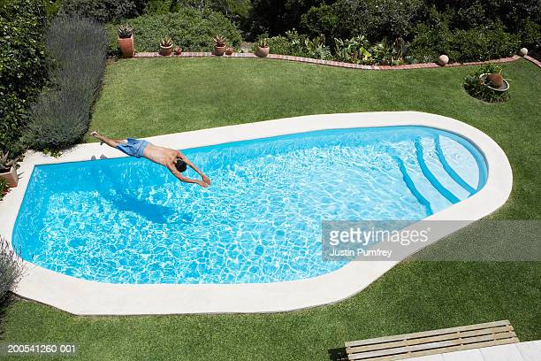 Man diving into swimming pool, elevated view