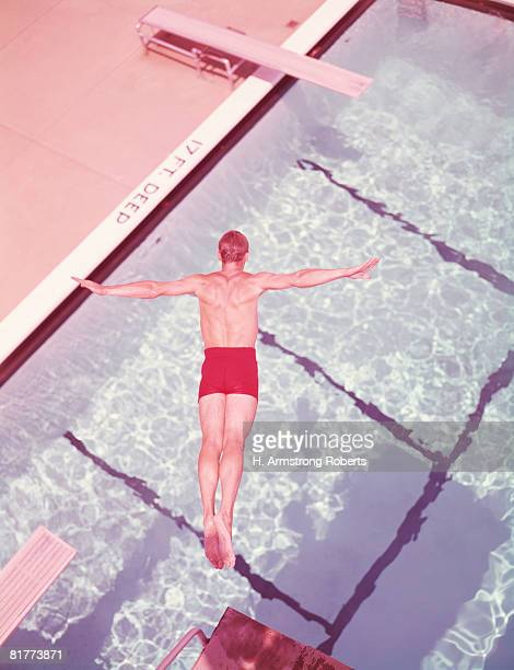 Man diving into swimming pool, overhead view. (Photo by H. Armstrong Roberts/Retrofile/Getty Images)