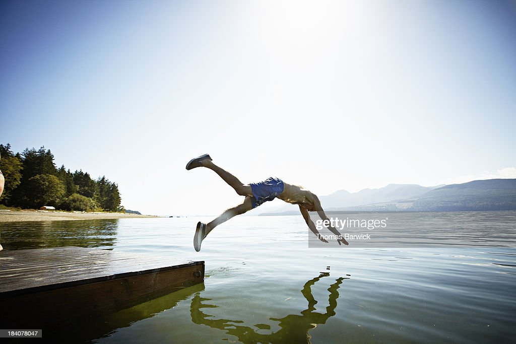 Man diving off floating dock into water