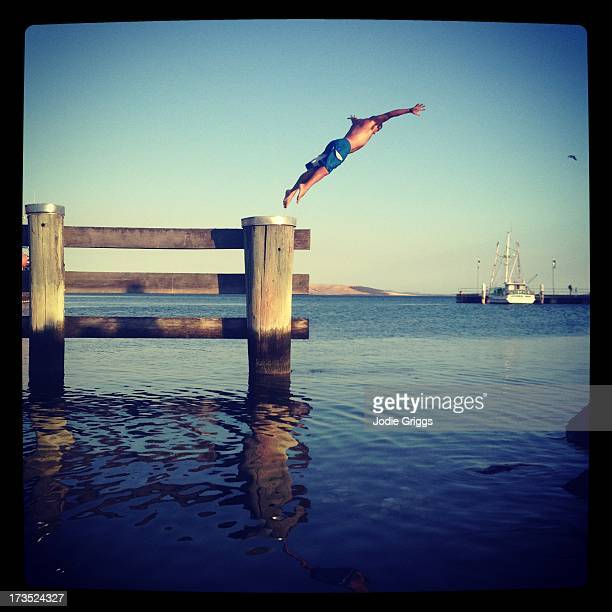 Man diving off wooden jetty into the water