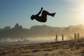 A man does a backflip on Ipanema beach on June 8 2014 in Rio de Janeiro Brazil