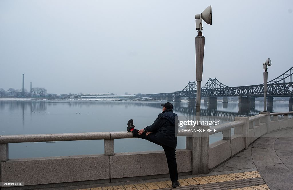 A man does his morning exercises along the banks of the Yalu River in the Chinese border town of Dandong, opposite to the North Korean town of Sinuiju, on February 8, 2016. The UN Security Council strongly condemned North Korea's rocket launch on February 7 and agreed to move quickly to impose new sanctions that will punish Pyongyang for 'these dangerous and serious violations.' With backing from China, Pyongyang's ally, the council again called for 'significant measures' during an emergency meeting held after North Korea said it had put a satellite into orbit with a rocket launch. AFP PHOTO / JOHANNES EISELE / AFP / JOHANNES EISELE