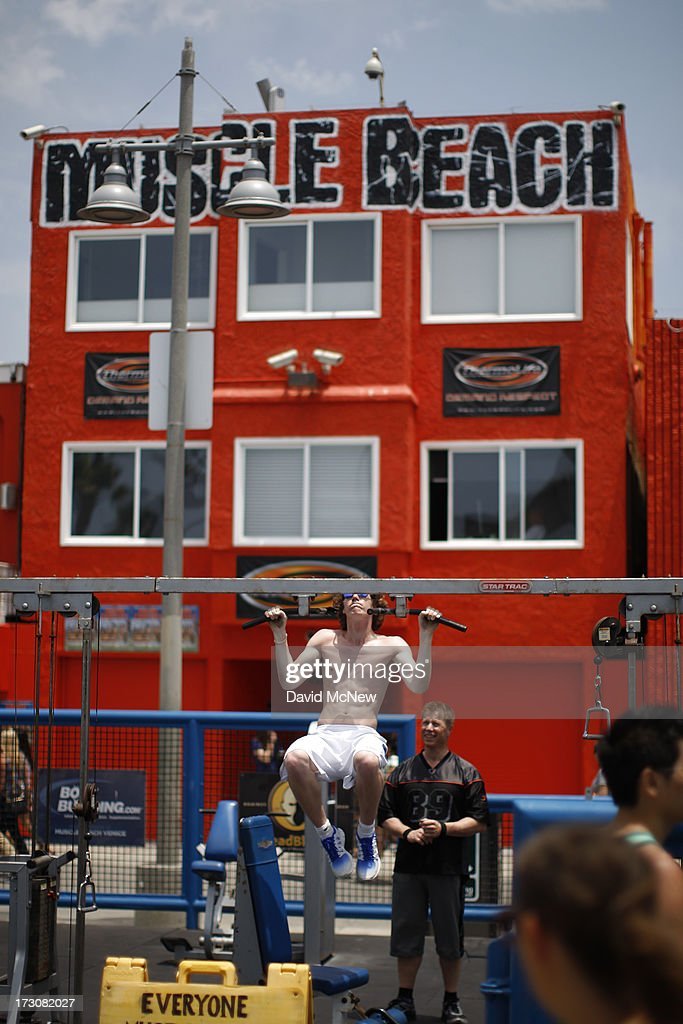 A man does pull-ups at the historic Muscle Beach workout area on Independence Day weekend at Venice Beach on July 6, 2013 in Venice, California. An estimated 16 million people visit the famous beach city annually which is celebrating 108th birthday as of July 4.