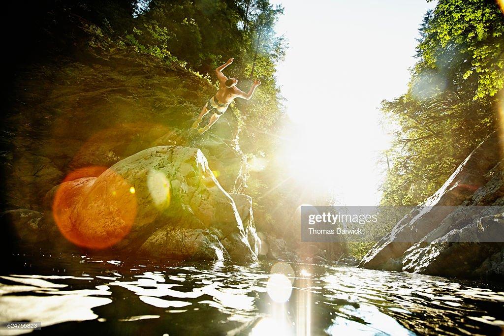 Man doing a backflip off of boulder into river