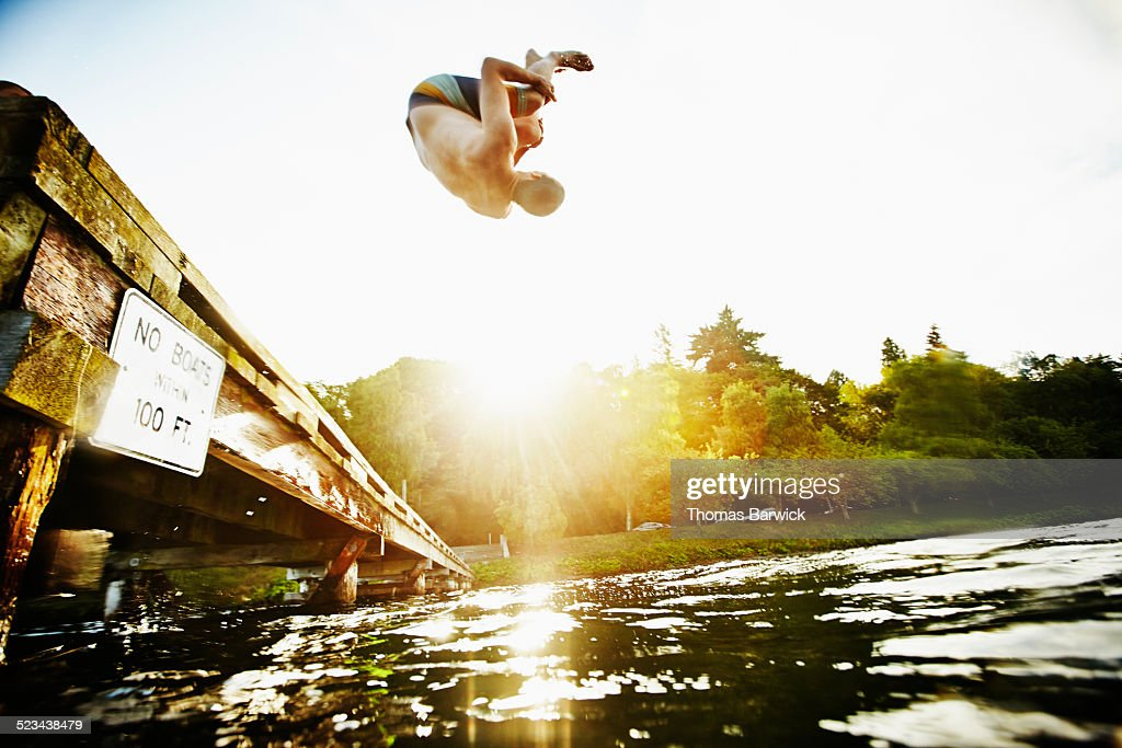 Man doing a backflip off of wooden dock into lake