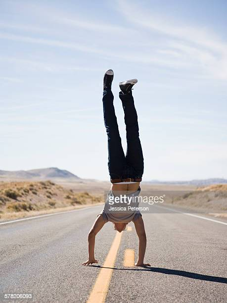 man doing a handstand in the middle of the road.