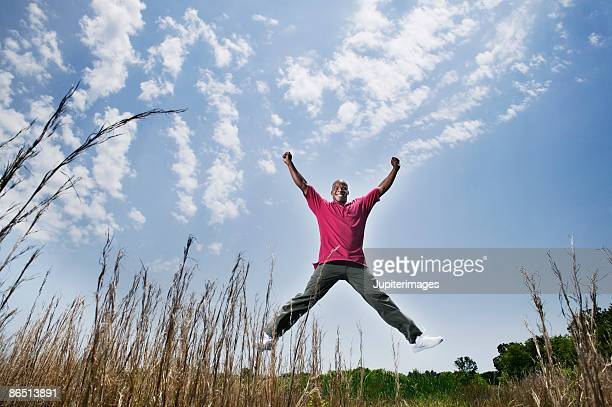 Man doing a jumping jack in field