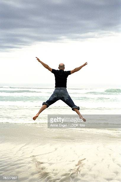 man doing a jumping jack on the beach