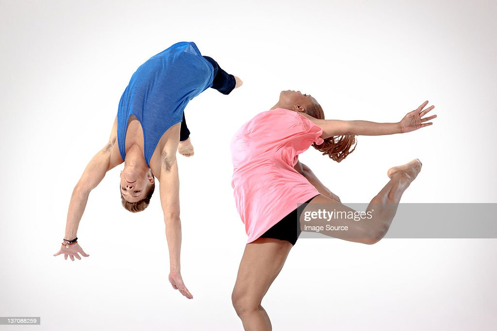 Man doing a somersault with woman jumping