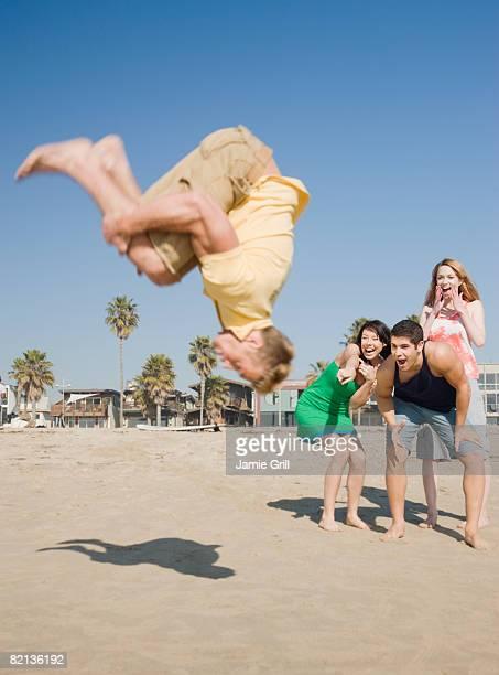 Man doing back flip on beach