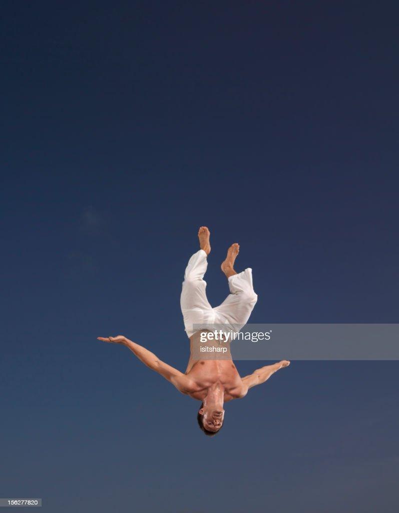Man Doing Back Flip on Blue Sky : Stock Photo