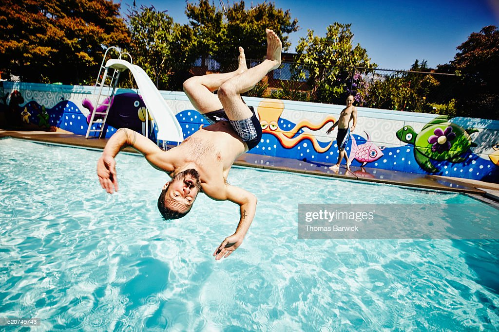 Man doing backflip into outdoor swimming pool : Stock Photo