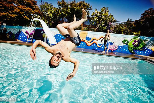 Man doing backflip into outdoor swimming pool