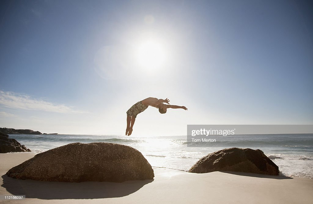 Man doing backflip on beach : Stock Photo